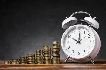 stack-increasing-coins-with-white-alarm-clock-wooden-desk-against-black-background